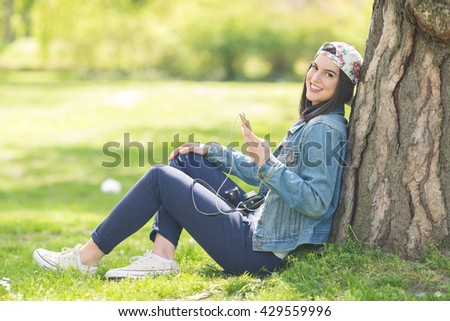 Teenage girl is relaxing in a park and using smart phone. She is leaning on a tree and listening to music on headphones.