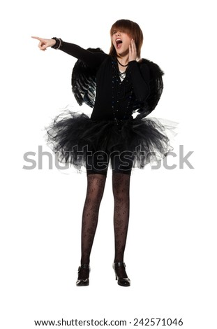 Teenage girl is wearing costume of black angel during masquerade party, isolated on white background. She points her finger to something, shouting and laughing - stock photo