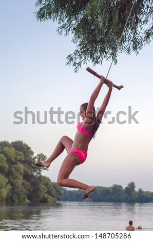 Teenage girl jumping into the river from the swinging rope on summer day. - stock photo