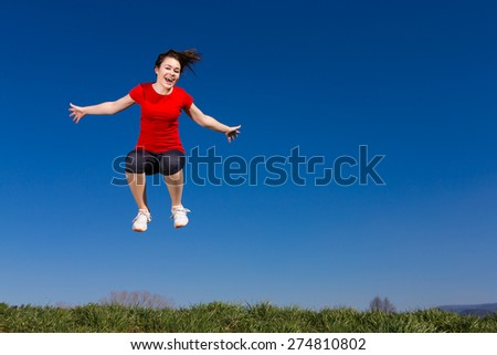 Teenage girl jumping, running outdoor against blue sky