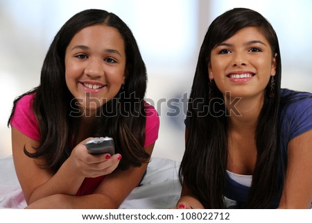 Teenage girl laying in her bed with her friend watching TV - stock photo