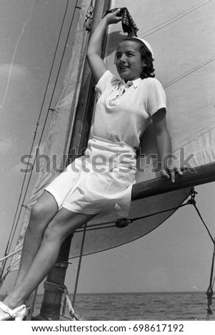Teenage girl leaning against boom with sail