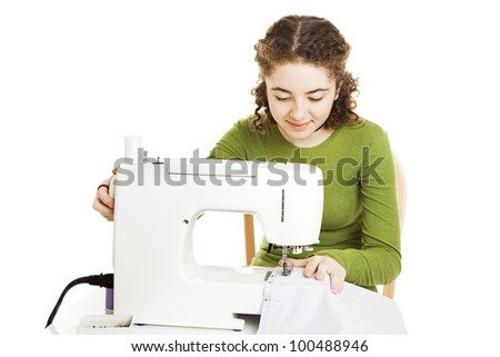 Teenage girl leaning how to use a sewing machine.  Isolated on white.