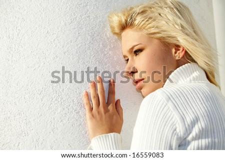 Teenage girl leaning to white wall, exterior