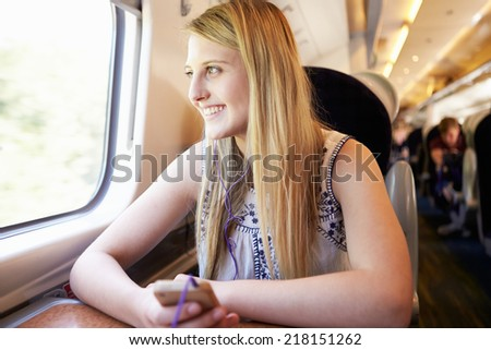 Teenage Girl Listening To Music On Train Journey