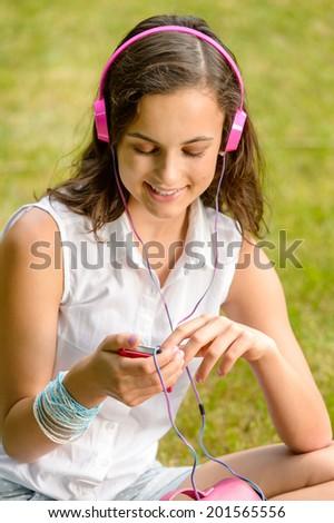 Teenage girl listening to music with headphones sitting on grass - stock photo