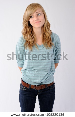 Teenage Girl Looking Bored. Thirteen year old girl standing with her hands behind her back looking to the side as if she is bored. Note: Not Isolated. - stock photo