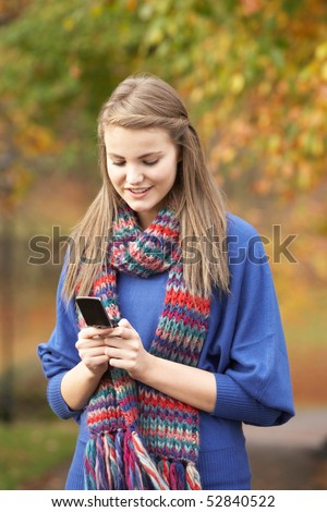 Teenage Girl Making Mobile Phone Call In Autumn Landscape - stock photo