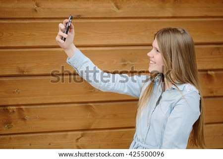 Teenage girl making selfie with a mobile phone on the wooden background - stock photo