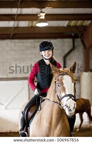 Teenage girl on horseback wearing helmet and safety vest in indoor arena - stock photo