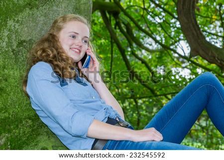 Teenage girl phoning mobile in green tree - stock photo