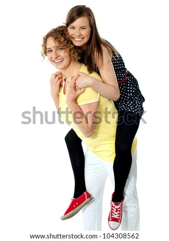 Teenage girl piggybacks her mother, studio shot - stock photo