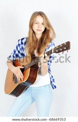 Teenage girl playing an acoustic guitar
