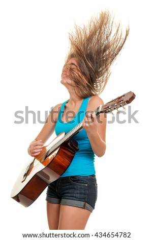 Teenage girl playing an acoustic guitar with her hair floating in the air - Isolated on a white background - stock photo
