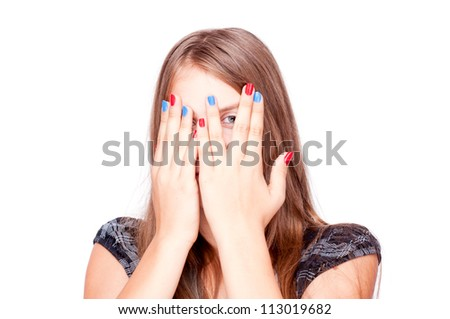 Teenage girl playing hide-and-seek and peek through fingers, isolated on white - stock photo
