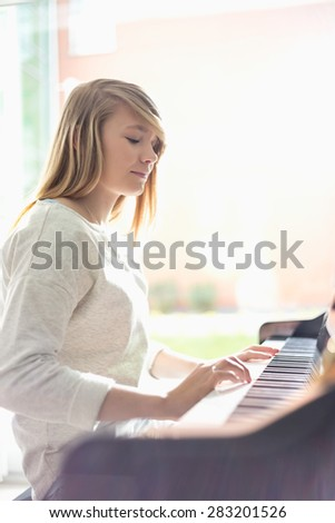 Teenage girl playing piano at home - stock photo