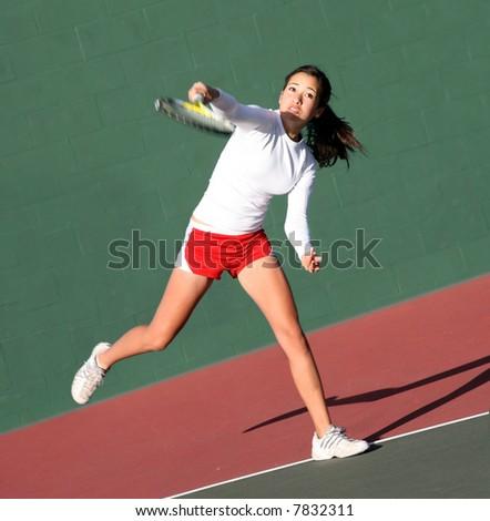 Teenage girl playing tennis - stock photo