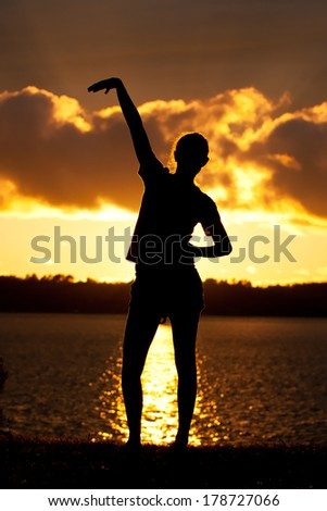 Teenage Girl Poses Silhouette Lake Background - stock photo