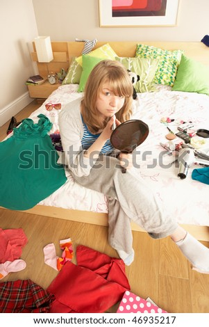 Teenage Girl Putting On Make Up In Untidy Bedroom - stock photo