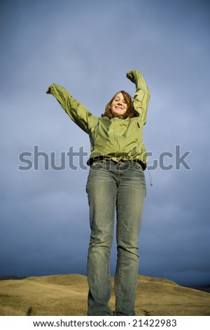 Teenage girl raising her arms as though in celebration or happiness - stock photo
