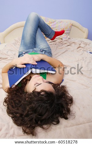 teenage girl reading a book on a bed - stock photo