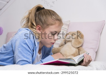 Teenage girl reading a book on the bed in a room.