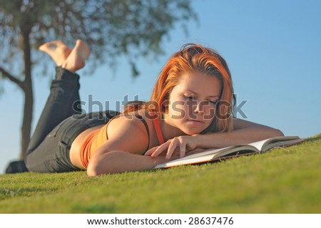 Teenage girl reading the book outdoors