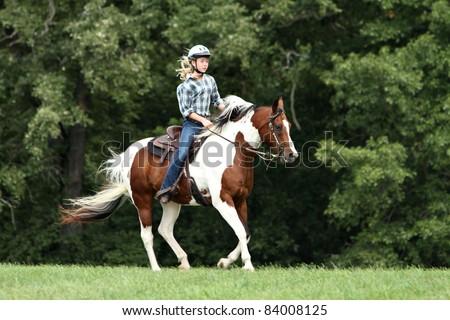 Teenage girl riding a running horse - stock photo