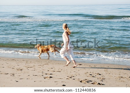 Teenage girl running along a beach shore with her golden retriever during the early morning. - stock photo