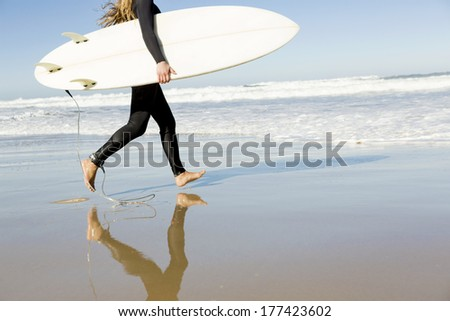 Teenage girl running on the beach with her surfboard - stock photo