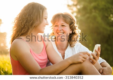 Teenage girl showing her mother photos on mobile phone outdoor in nature with setting sun in background - stock photo