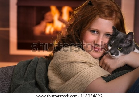 Teenage girl sitting at fireplace at home cuddling cat smiling. - stock photo