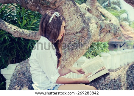 Teenage girl sitting on a big tree and reading a book - stock photo