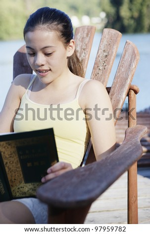 Teenage girl sitting on deck by lake reading - stock photo