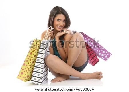 Teenage girl sitting on floor with shopping bags - stock photo