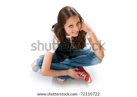 Teenage girl sitting on the floor. Isolated on white - stock photo