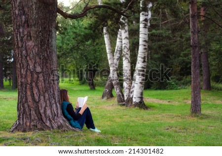 Teenage girl sitting under the tree and reading book on cloudy autumn day.