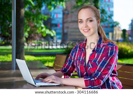 teenage girl sitting with laptop in summer cafe - stock photo