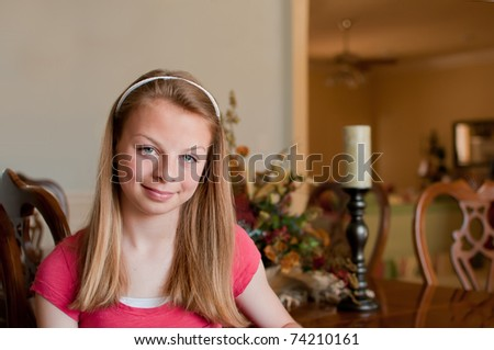 Teenage girl sitting with left side showing at wood finished dining room table at grandparents house with table decorations - stock photo
