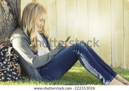 Teenage girl smiling while using a cell phone, texting, surfing the internet or playing a game, in an outdoor setting. - stock photo