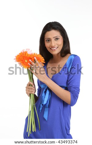 Teenage girl standing with orange daisy flowers