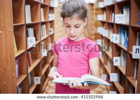 Teenage girl stands between bookcases in library and reads book. - stock photo