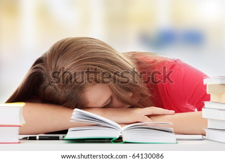 Teenage girl studying at the desk being tired - stock photo