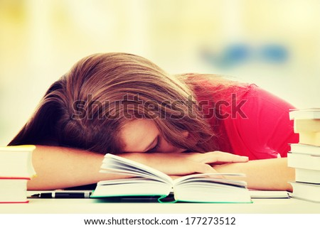 Teenage girl studying at the desk being tired, isolated on white  - stock photo