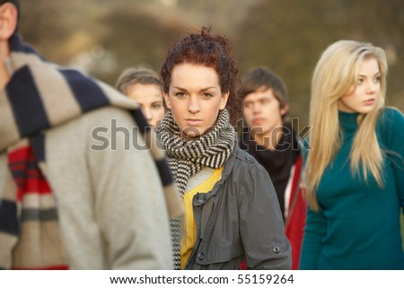 Teenage Girl Surrounded By Friends In Outdoor Autumn Landscape - stock photo