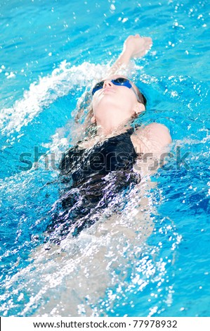teenage girl swimming in swim meet doing backstroke