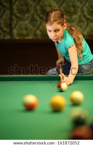 Teenage girl takes aim at a ball sitting on the pool table