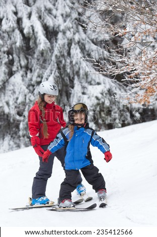 Teenage girl trains  her little sister to ski on the slope in the mountains - stock photo