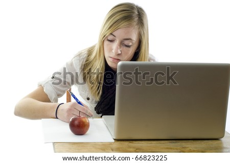 Teenage girl uses her laptop, pen and papers to complete her homework. - stock photo