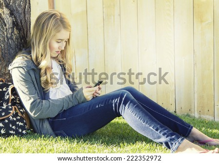 Teenage girl using a cell phone, texting, surfing the internet or playing a game, in an outdoor setting.